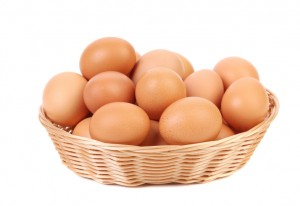 Brown eggs in the basket on a white.